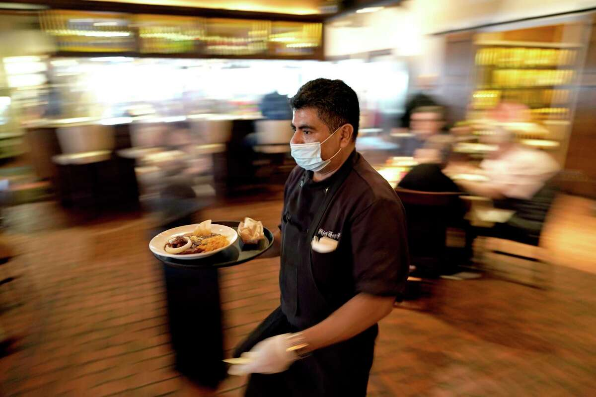 A restaurant worker wears a face mask as he delivers food to a table.