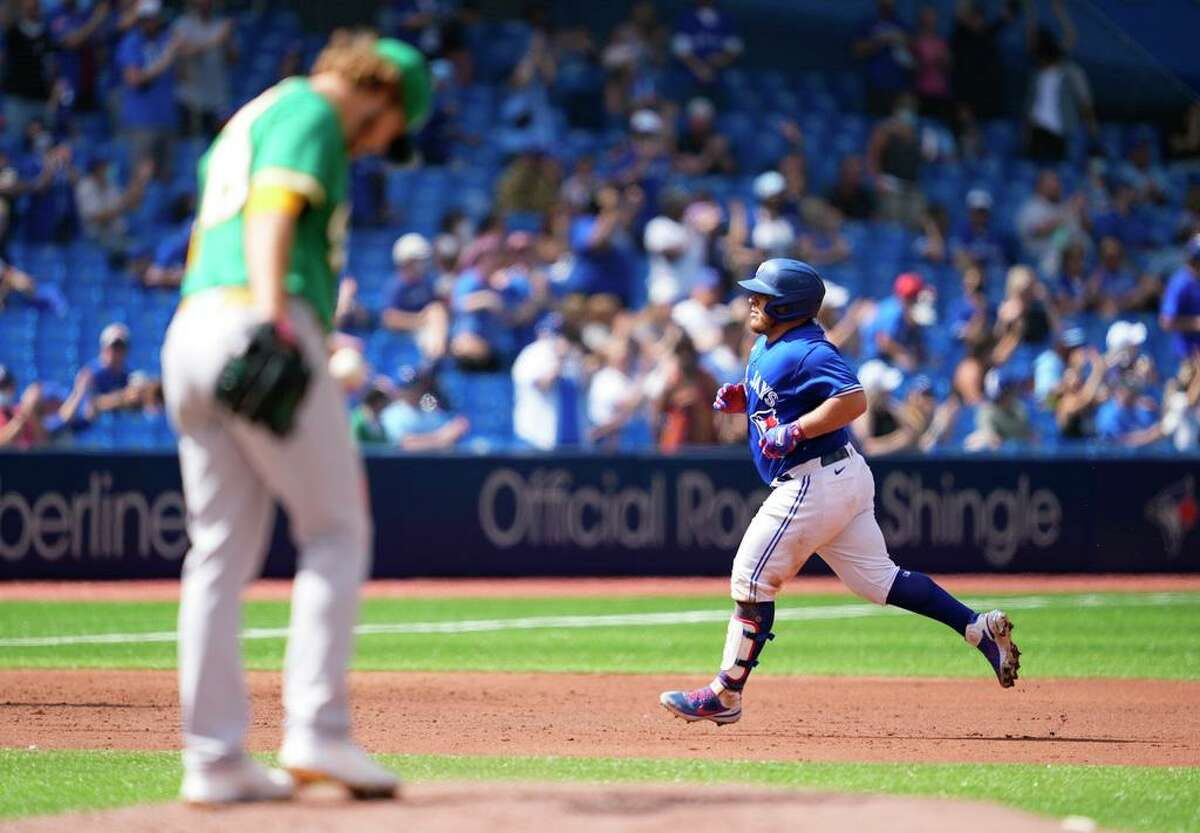TORONTO, ONTARIO - SEPTEMBER 5: Alejandro Kirk #30 of the Toronto Blue Jays runs the bases after hitting a home run behind Cole Irvin #19 of the Oakland Athletics in the second inning during their MLB game at the Rogers Centre on September 5, 2021 in Toronto, Ontario, Canada. (Photo by Mark Blinch/Getty Images)