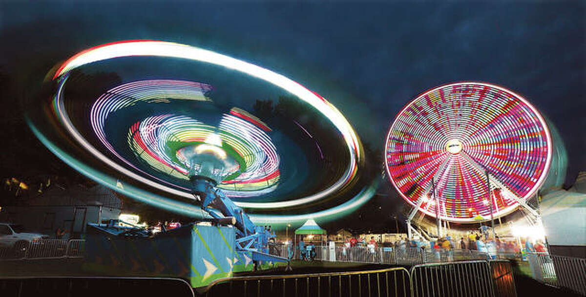 The moving lights of the Hang Glider ride, left, and the Luehrs' large Ferris Wheel light up the night sky at the Bethalto Homecoming this past weekend. The annual event runs through Monday.