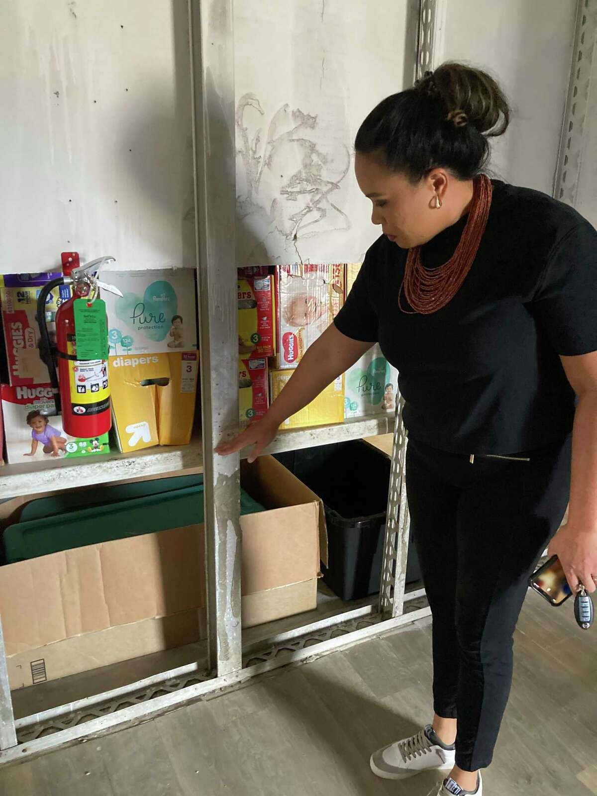 Deborah Tomov, Executive Director of Family Services of Southeast Texas, demonstrates how high the water came up to when Hurricane Imelda flooded their shelter. The height, she said, is one in which babies and children can easily drown.