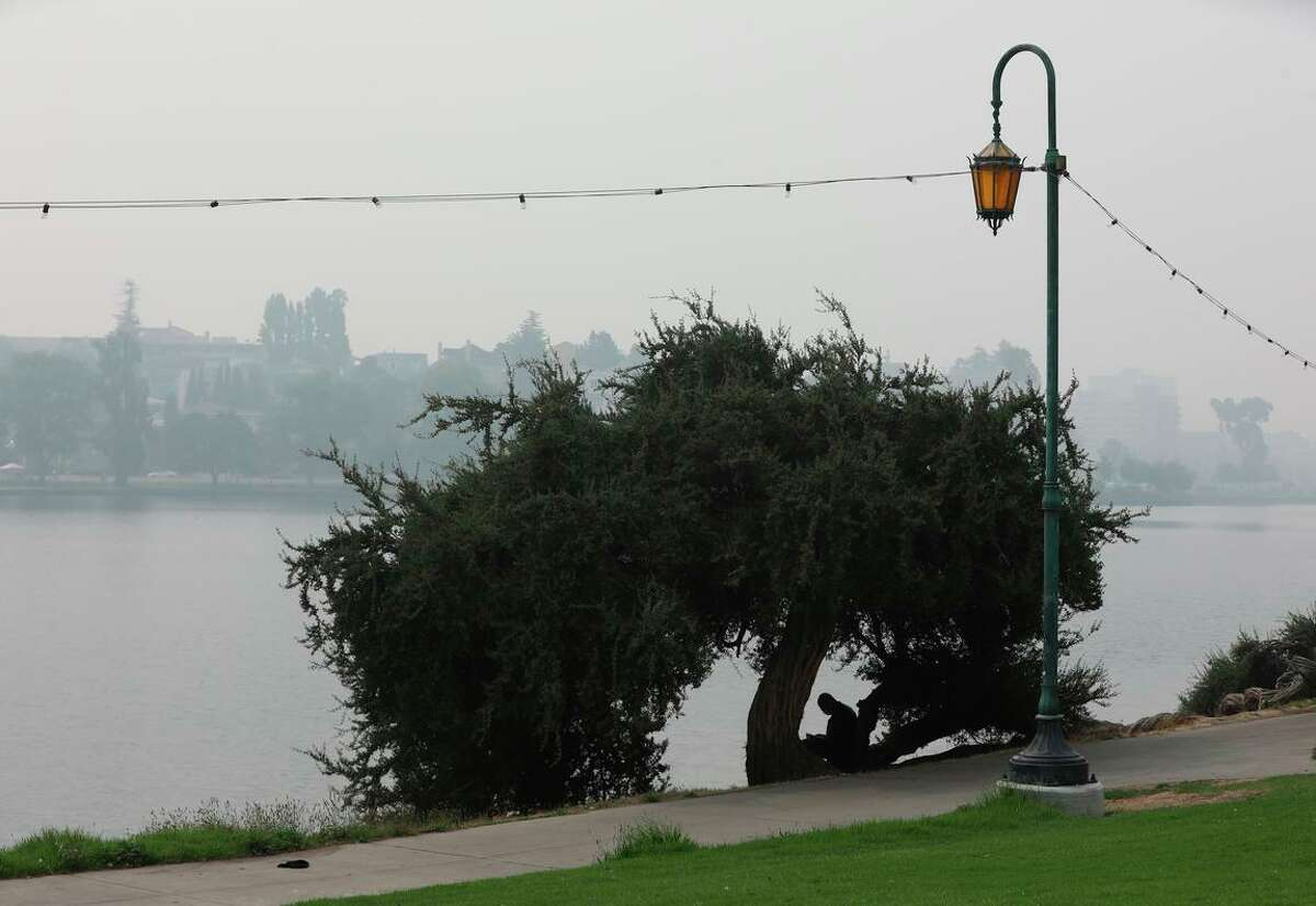 A man relaxes under a tree at Lake Merritt under Oakland skies clouded with wildfire smoke last September. The Bay Area forecast for Labor Day includess moky skies and high temperatures.