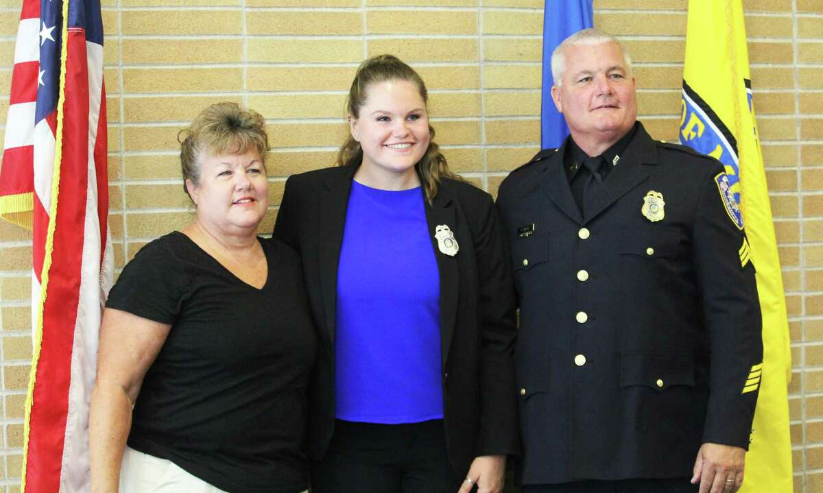 The Middletown Police Department welcomed six new officers Friday morning in a ceremony at City Hall Council Chambers. From left are recently retired officer Brenda White, her niece Kelsey White, and Sgt. Brian White, Kelsey White's father. Kelsey White's grandfather, the late officer Douglas White, died last year.