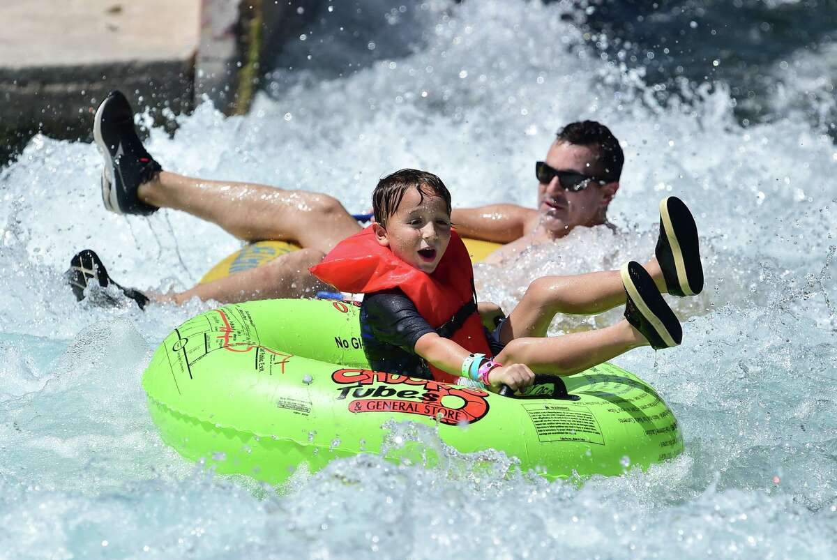 A youngster laughs as he bounces through the tube chute on the Comal River in New Braunfels on Sunday during the summer season's last big weekend.