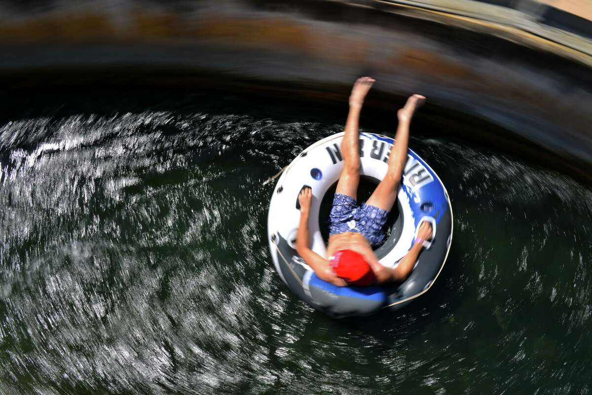 A tuber spins through the tube chute on the Comal River in New Braunfels on Sunday during the summer season's last big weekend. .