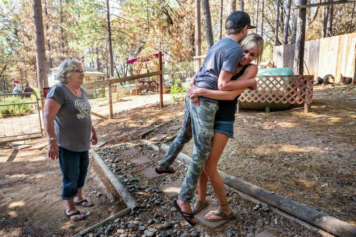 Jacquie Odling (left) and her family had to evacuate for 18 days due to the Caldor Fire, staying in 5 different motels. But they were able to return to a their Caldor Road home to find their home was untouched by the flames. Her grandson Matt, embraced by his mother Tiffany Odling, didn't mind too much since some of the motels had swimming pools.