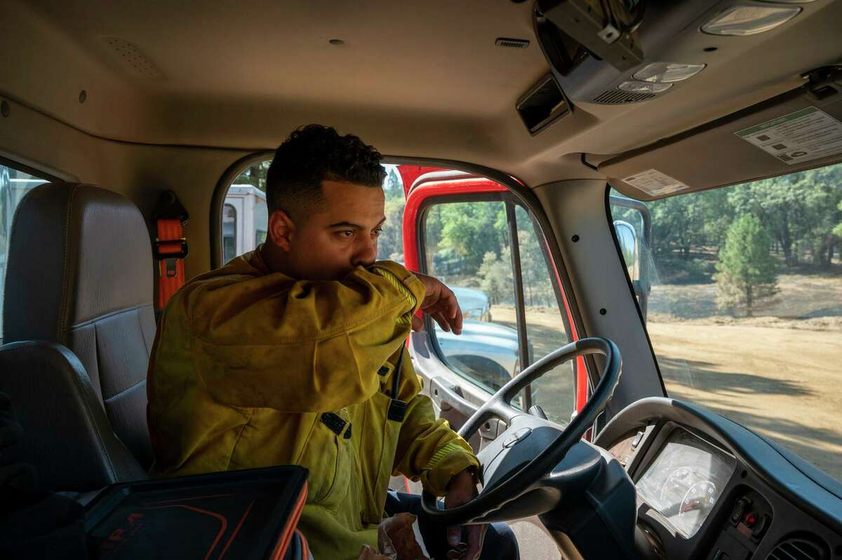 Firefighter Anthony Pedro works out of the Grizzly Flats fire station, which has burned to the ground. He replenishes water for the firefighters.