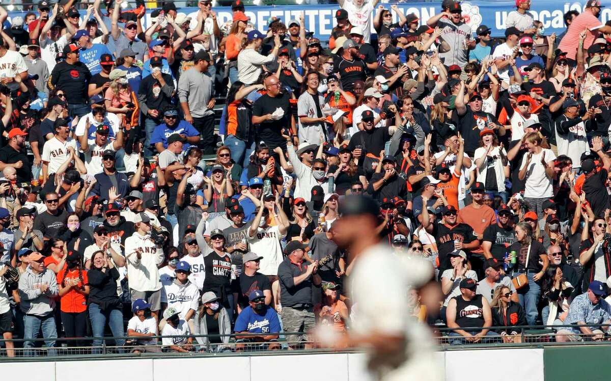 San Francisco Giants' fans react as Brandon Belt rounds the bases after hitting a solo home run against the Dodgers' Walker Buehler at Oracle Park on September 5, 2021.