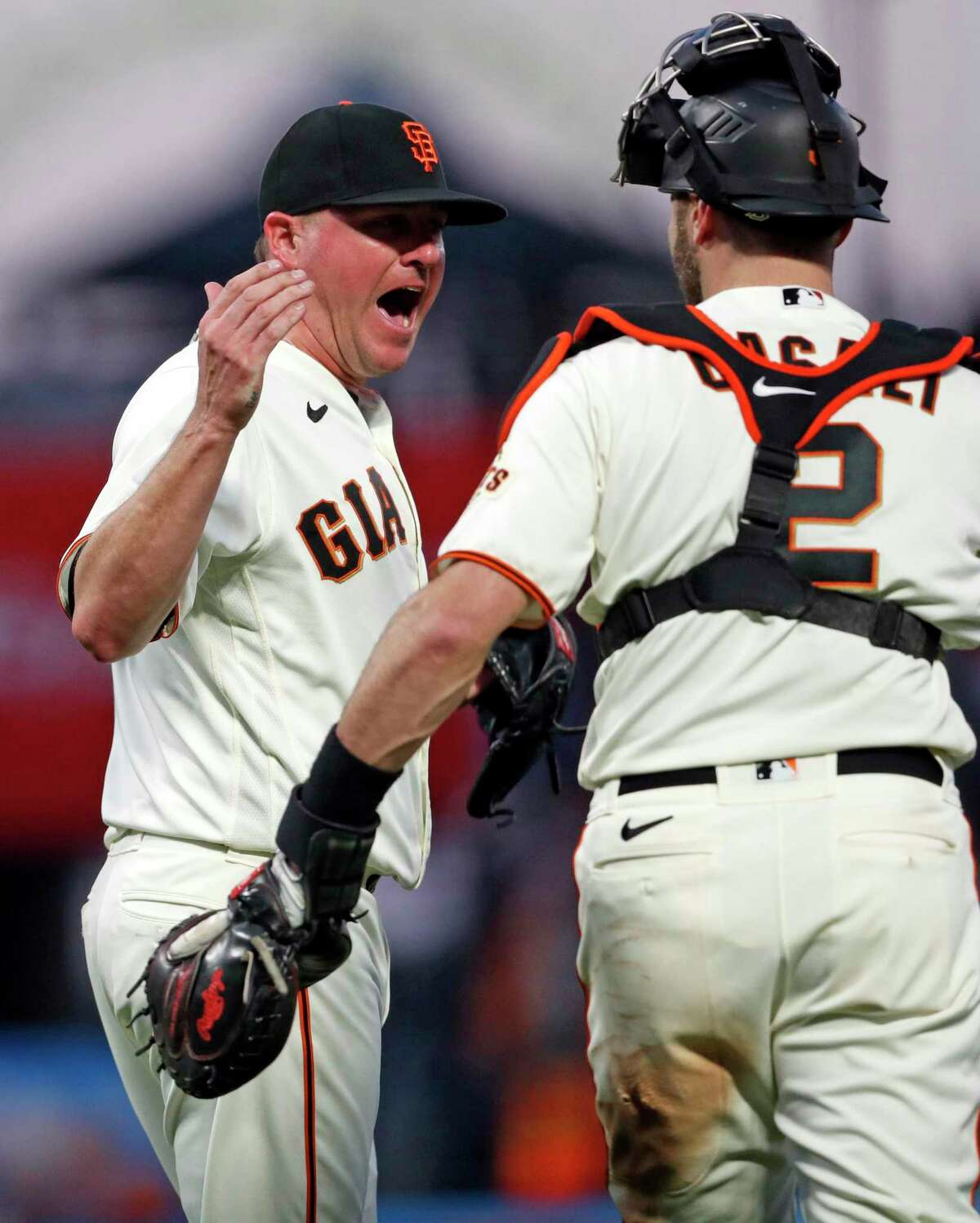 San Francisco Giants' Jake McGee and Curt Casali celebrate 6-4 win over Los Angeles Dodgers in MLB game at Oracle Park in San Francisco.