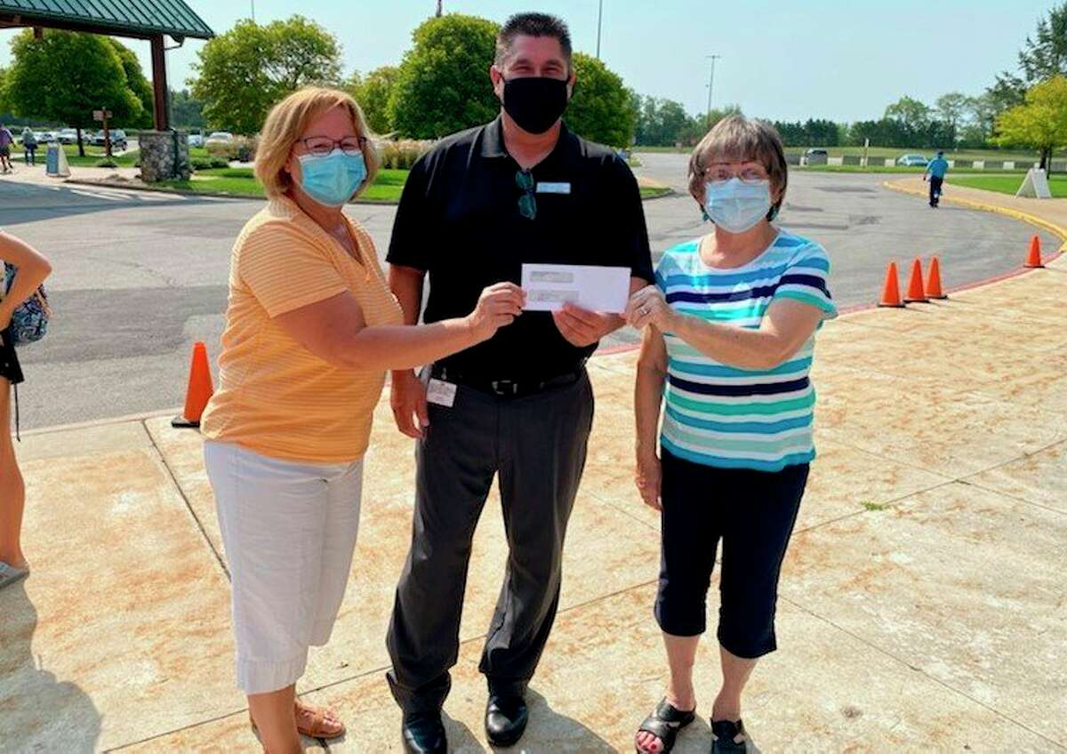 Michelle Grassa (left) and Joan Gamache (right), of the Matthew 25:35 Food Pantry, accept a donation from Chad Eckhardt, player development managerfor the Little River Casino Resort. The funds were raised by theLRCR Charity Golf Outing, which took place in July. (Courtesy photo)