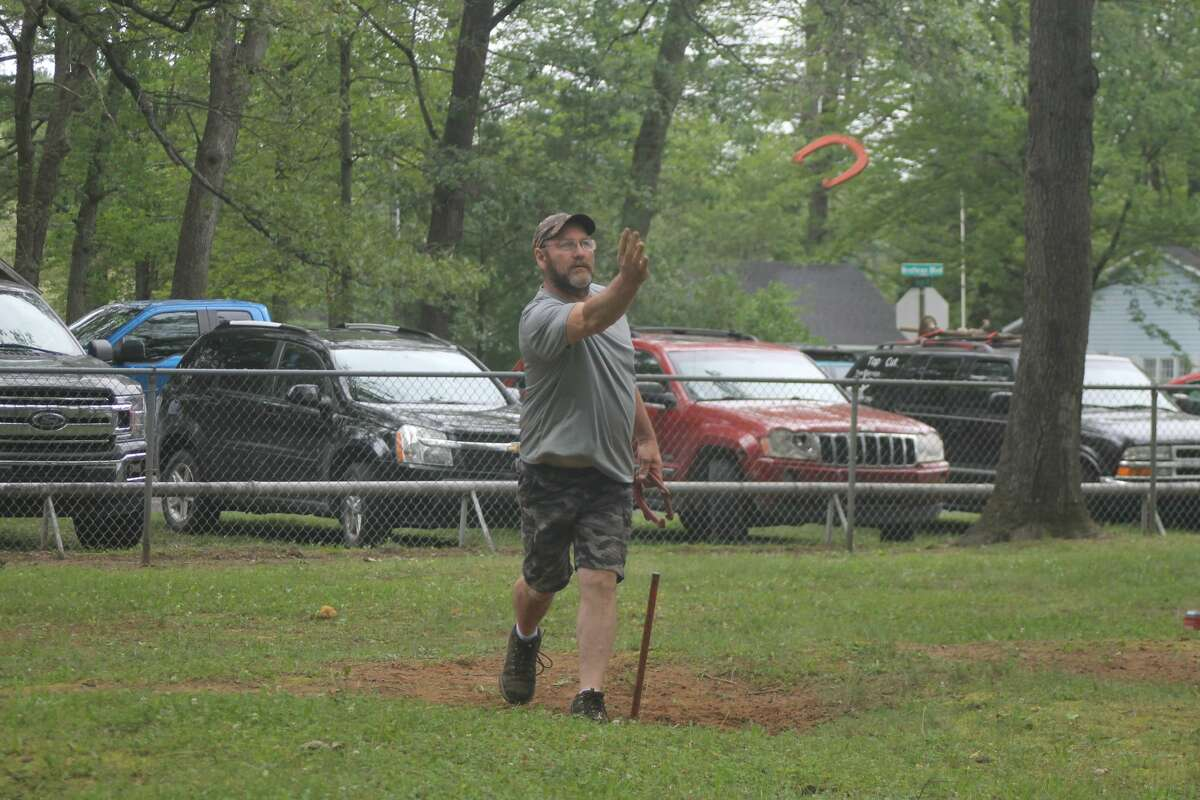 A man tosses a horseshoe in Dickson Township Park during Brethren Days. Many speculate the game of horseshoes can be traced back to the Roman Empire.