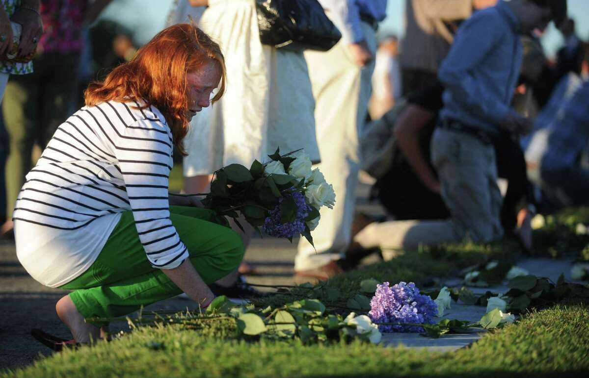 Emma Hunt, 12, of Essex, places flowers on her father's name at Connecticut's 9/11 Living Memorial during the 11th annual 9/11 Memorial Service Monday, September 10, 2012 at Sherwood Island State Park in Westport, Conn. William Christopher Hunt, of Norwalk, died in 2 Tower World Trade Center.