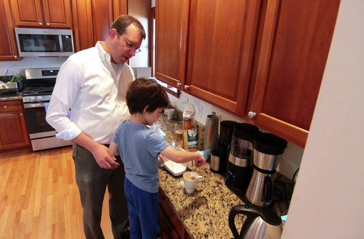 Matthew Lee, 3, helps his dad Ben make coffee together at his home in Stamford, Conn., on Saturday Sentember 4, 2021. Lee, who is a City Rep., D-15, also served in the U.S. Army and worked closely with a translator while in Afghanistan. He recently helped the translator's family flee the country on one of the last military flights out.