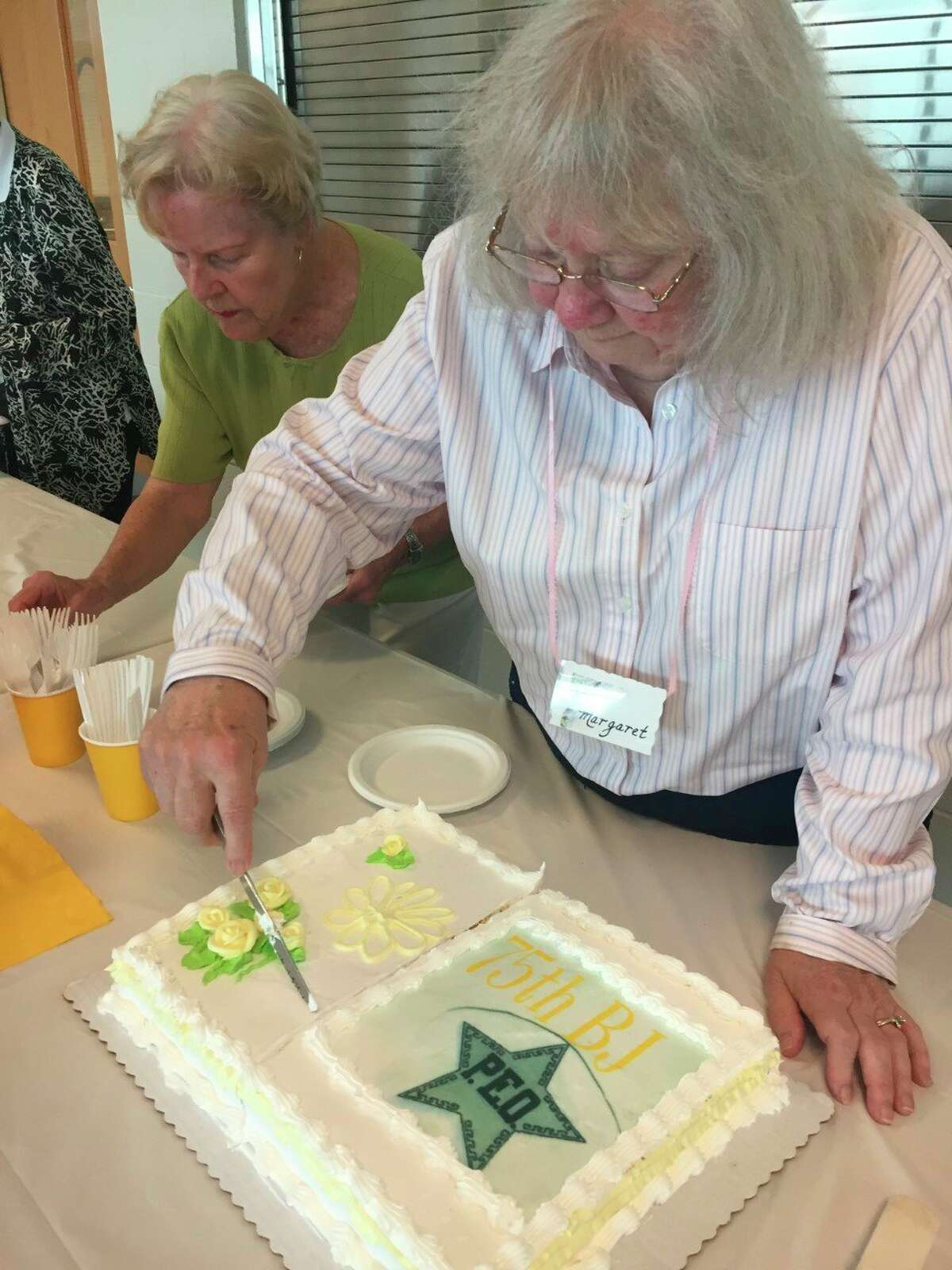 Margaret Beery cuts the anniversary cakewith Barb Baltazar's help during a75th anniversary teafor theChapter BJ of P.E.O. in Frankforton Aug. 11 at St. Andrew's Presbyterian Church in Beulah. (Courtesy Photo)