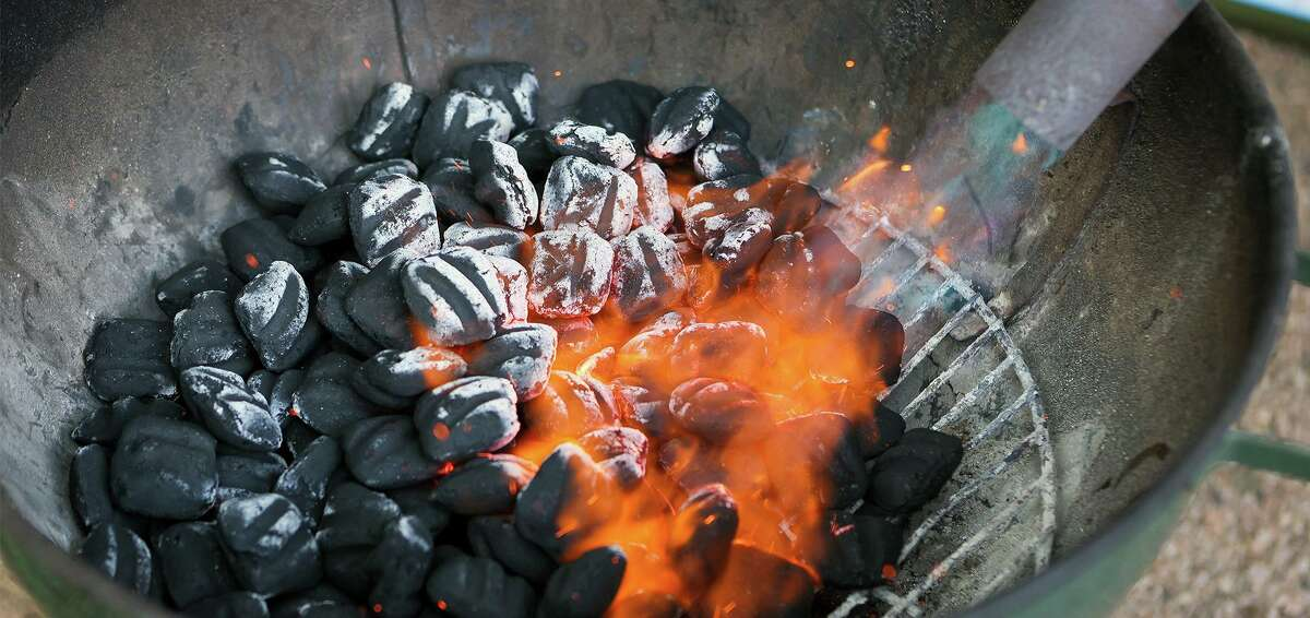 A full configuration of charcoal briquettes is ignited with a propane torch.