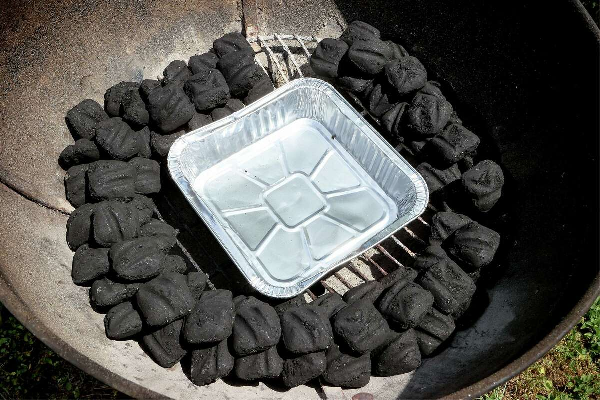 The snake configuration of charcoal in a grill provides enough heat for 10 hours as it burns from one end to the other. The pan inside can collect fat drippings or, when filled with water, provide moisture.