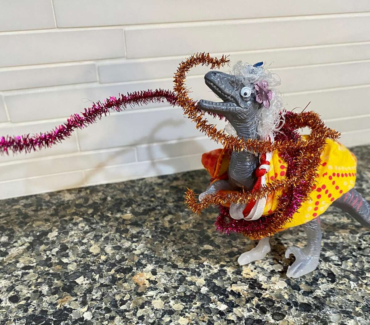 This is Granny Raptor in her homemade dress, made from a repurposed cloth face mask and sparkly pipe cleaners.