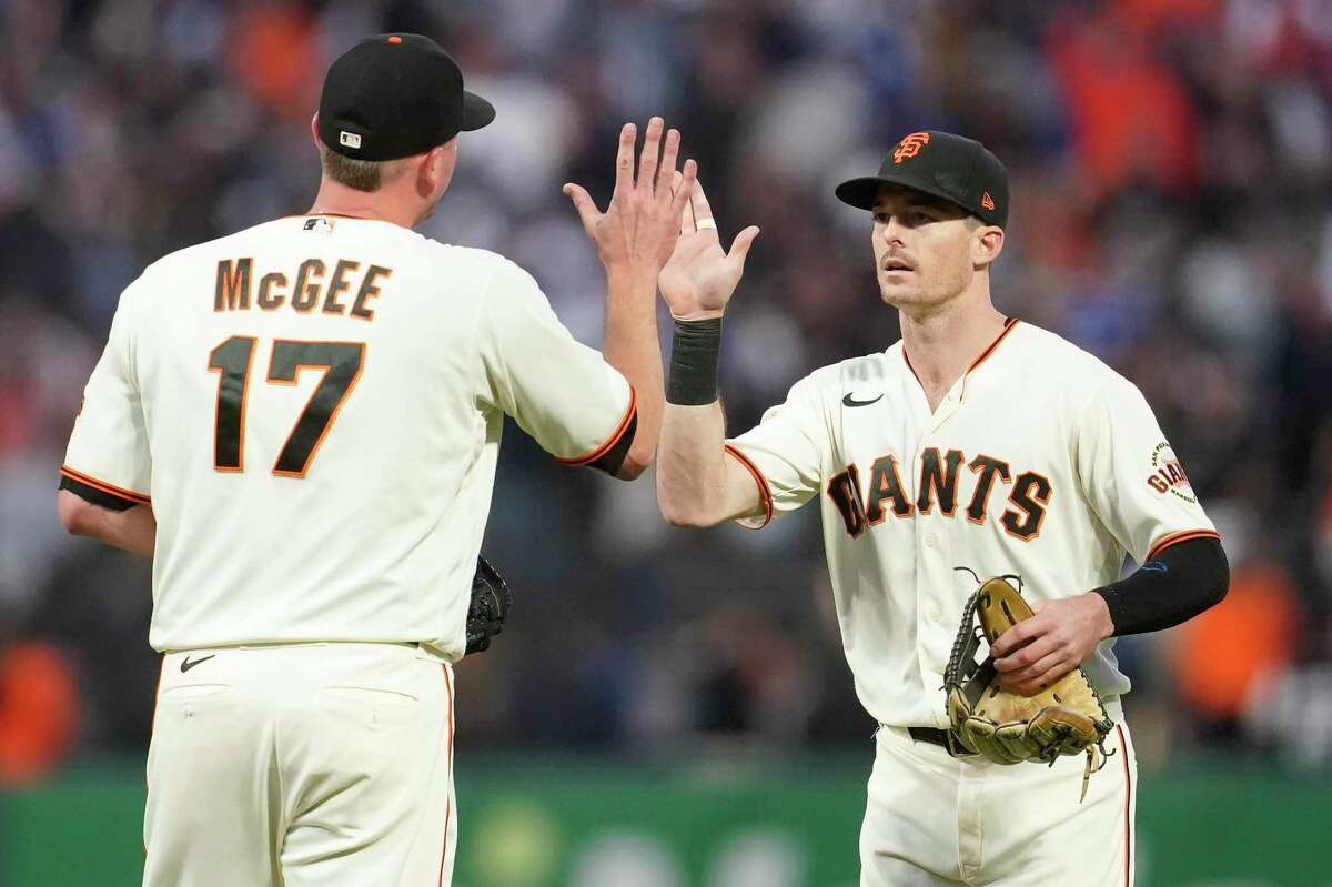 San Francisco Giants pitcher Jake McGee (17) celebrates with Mike Yastrzemski after the Giants defeated the Los Angeles Dodgers in a baseball game in San Francisco, Sunday, Sept. 5, 2021. (AP Photo/Jeff Chiu)