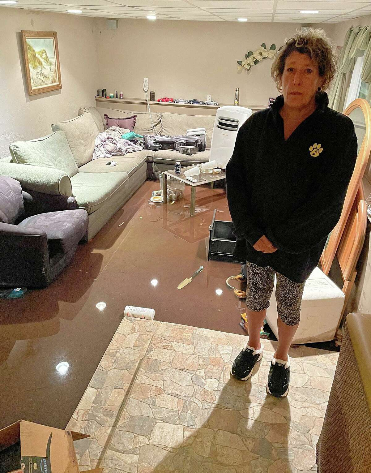 Marianne McGee stands on a step leading to her downstairs living area, flooded by Storm Ida. Friday, Sept. 3, 2021.