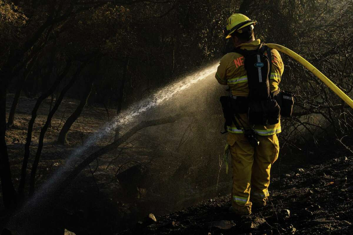 A firefighter puts out Bridge Fire spot fires burning near the Foresthill bridge in Auburn on Sunday.