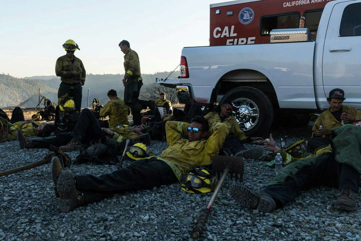 Crew members from the Nevada-Yuba-Placer Army National Guard take a break after battling the Bridge Fire throughout the day on Sunday, September 5, 2021. The fire is burning in the Foresthill Bridge area in Placer County.