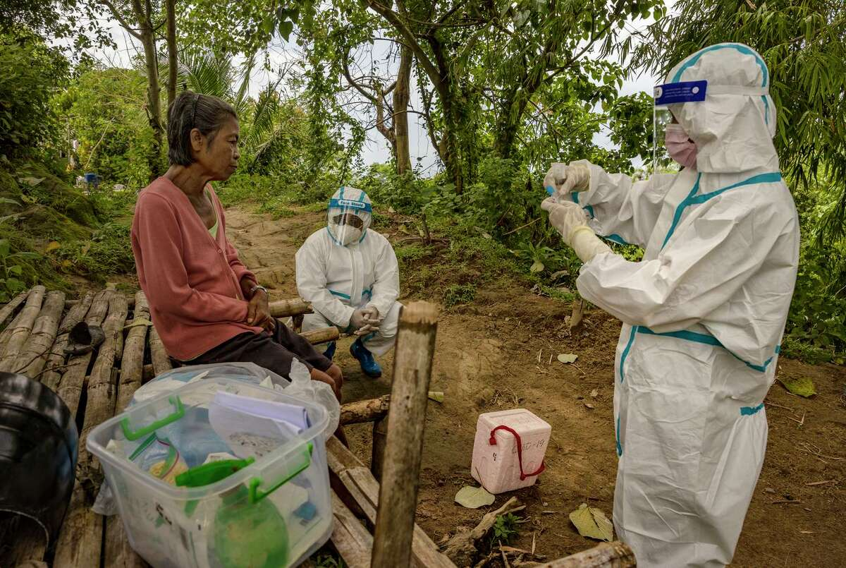 Health care workers test a resident of a Philippine mountain village for the coronavirus.