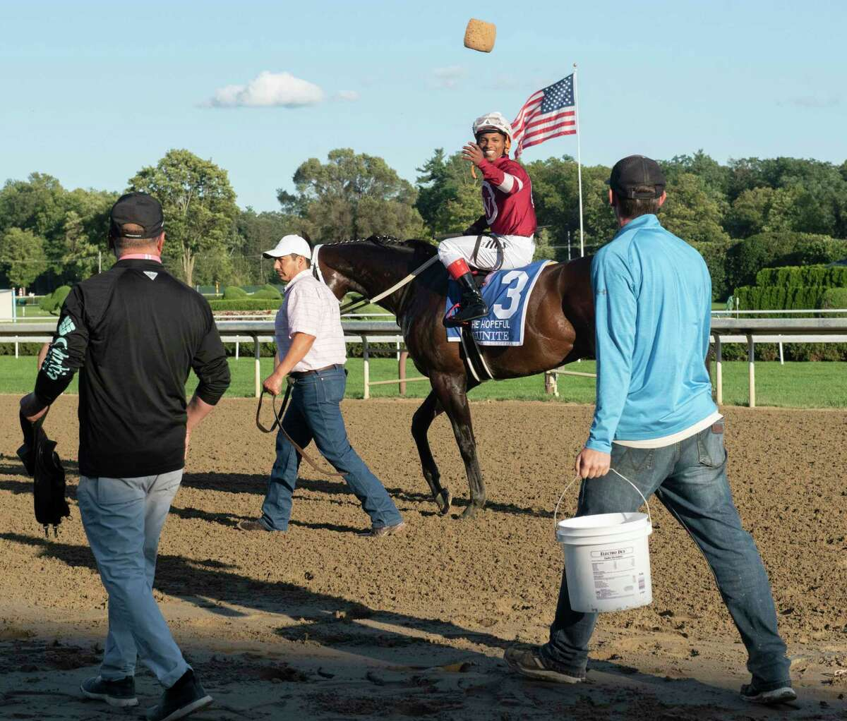Jockey Ricardo Santana, Jr. throws a sponge to a worker after cooling Gunite who crossed the finish line in first place during The Hopeful feature race at Saratoga Race Course on Monday, Sept. 6, 2021 in Saratoga Springs, N.Y. Today is the last day of the meet.