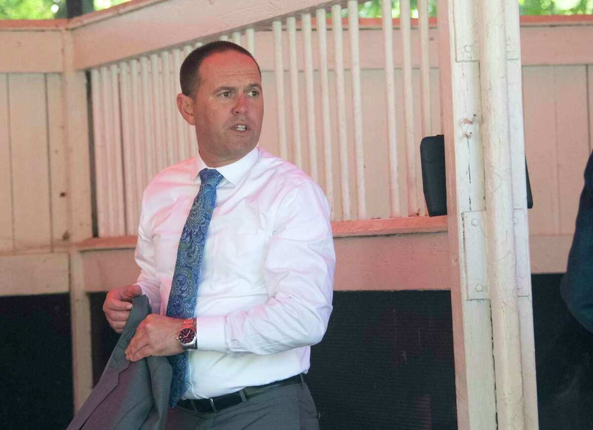 Trainer Chad Brown puts his jacket back on after checking a horse in a stall in the paddock area at the Saratoga Race Course on Monday, Sept. 6, 2021 in Saratoga Springs, N.Y. Today is the last day of the meet.