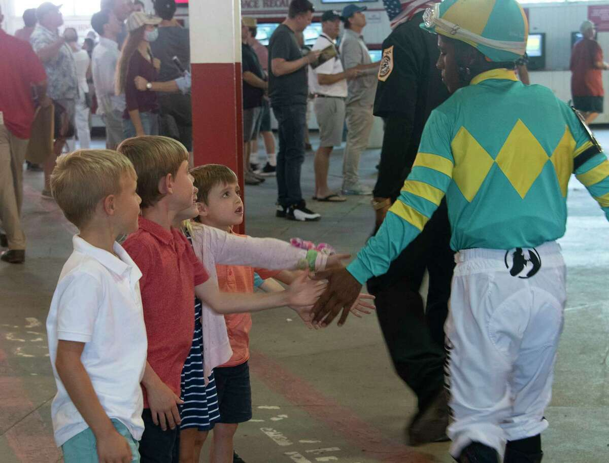 Young race fans, not old enough to bet, get a hand slap from jockey Ricardo Santana, Jr. after the 5th race at Saratoga Race Course. The fans were back after being shut out in 2020 and the jockeys and trainers appreciated the return.