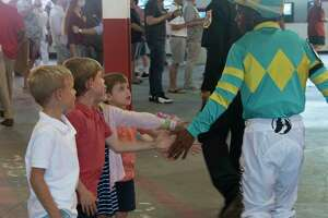 Young race fans, not old enough to bet, get a hand slap from jockey Ricardo Santana, Jr. after the 5th race at the Saratoga Race Course on Monday, Sept. 6, 2021 in Saratoga Springs, N.Y. Today was the last day of the meet.