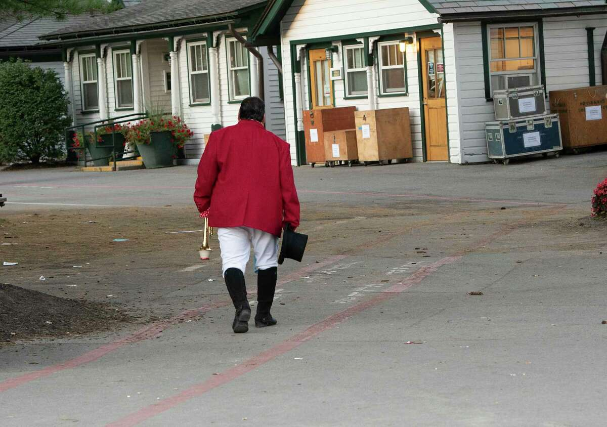 """Sam """"The Bugler"""" Grossman is seen walking back to the silks room after announcing the last """"Call to the Post"""" for the season at Saratoga Race Course on Monday, Sept. 6, 2021 in Saratoga Springs, N.Y."""