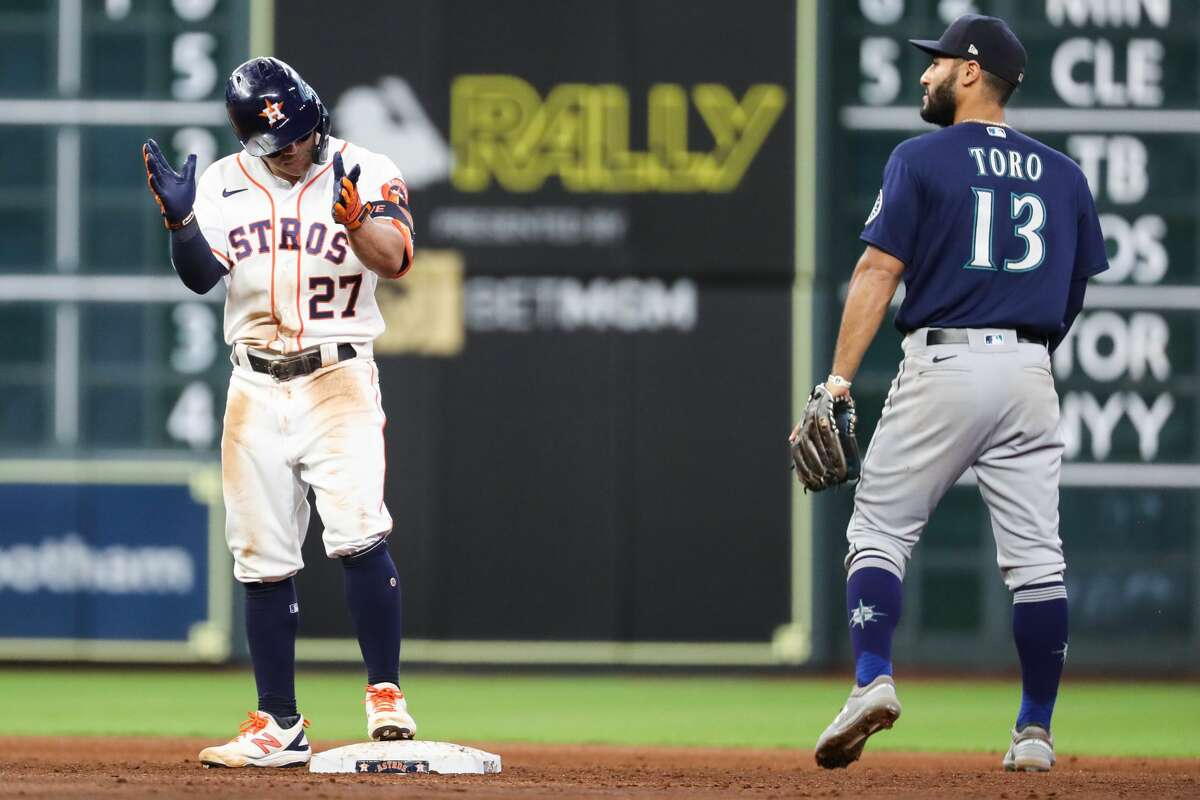Houston Astros Jose Altuve (27) reacts after standing on second with Seattle Mariners Abraham Toro (13) after hitting a double during the second inning of a major league baseball game Monday, Sept. 6, 2021, at Minute Maid Park in Houston.