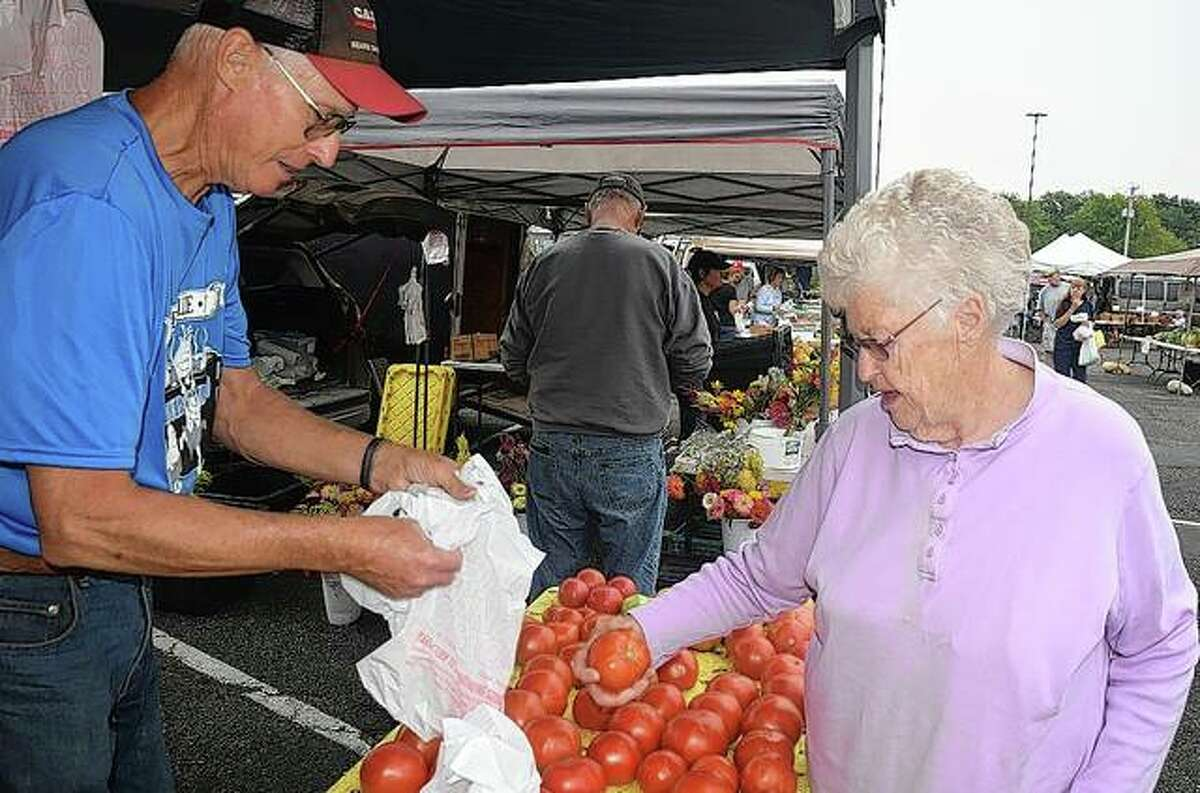 Carol Grady selects tomatoes to buy from Bernie Meyer at this weekend's farmers' market at Lincoln Square in Jacksonville.