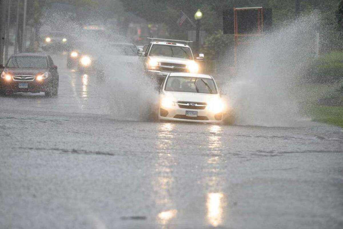 A car drives through flooded area on Main Street as the remnants of Tropical Depression Ida brought heavy rains to Danbury, Conn., on Wednesday, Sept. 1, 2021.