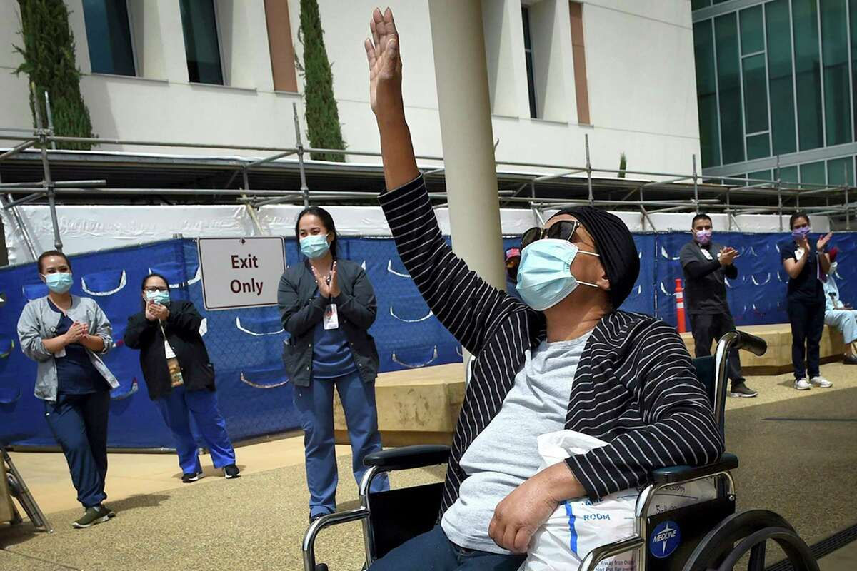 """In this May 19, 2020, file photo, Karen Parker-Bryant, 64, raises a hand skyward after she was released from Clovis Community Hospital after a battle with COVID-19, in Fresno, Calif. Hospitals in the heart of California's Central Valley are running out of beds in their intensive care units because of an influx of coronavirus patients, prompting officials on Friday, Sept. 3, 2021, to declare an official """"surge."""" (John Walker/The Fresno Bee via AP, File)"""