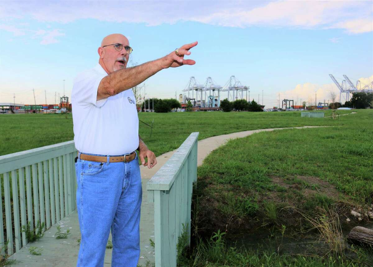 Morgan's Point Mayor Michel Bechtel gestures toward an area where native trees and prairie grass will be planted at the Col. James Morgan New Washington Prairie. The Barbours Cut Container Terminal is in the background.