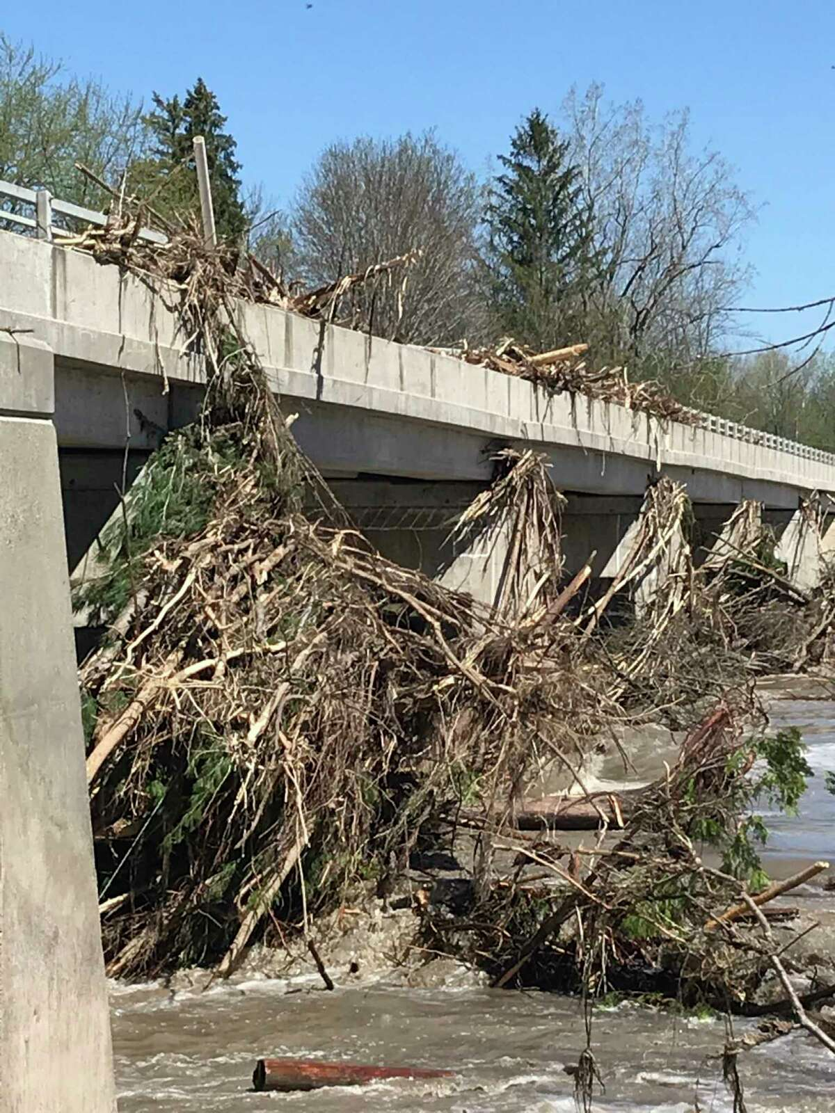 Pictured is the M-30 bridge over the Tittabawassee River, just north of Edenville, with trees and debris on top of the bridge, shortly after the May 19, 2020 dam failures. The bridge was repaired and reopened in September 2020. (Photo courtesy of Michigan Department of Transportation)