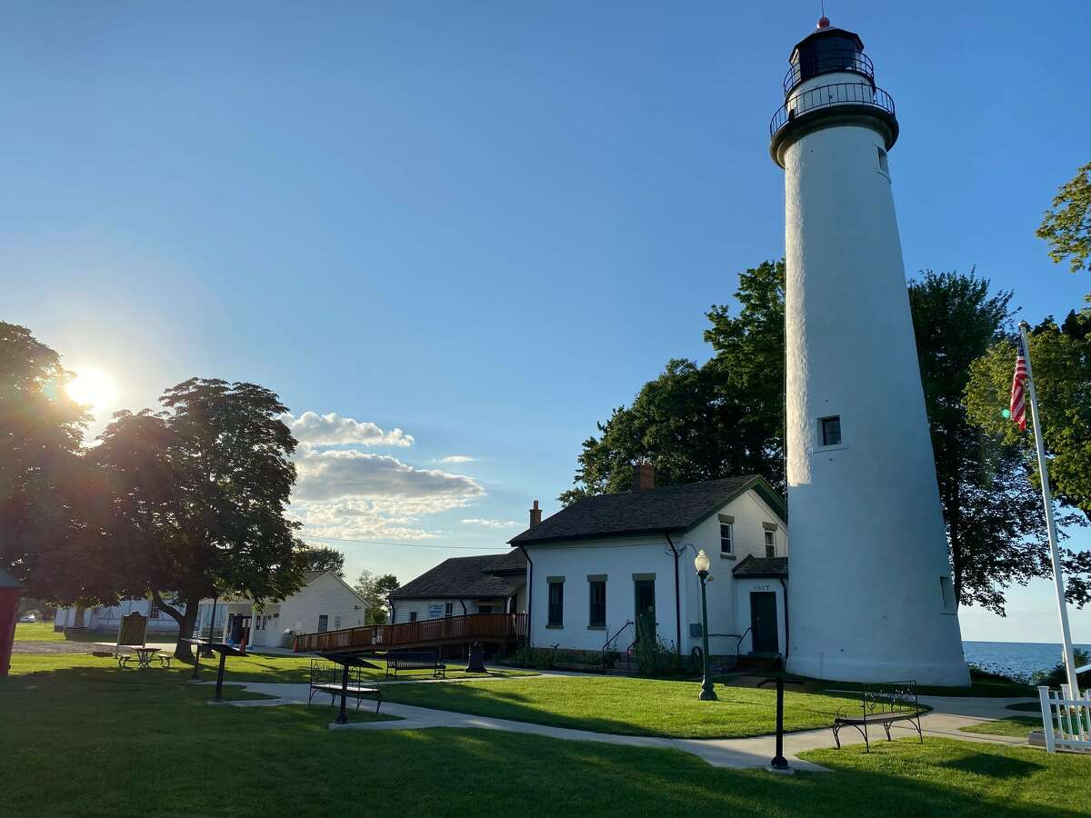 The sun peeks through the clouds over Point aux Barques lighthouse near Huron City on a recent afternoon.