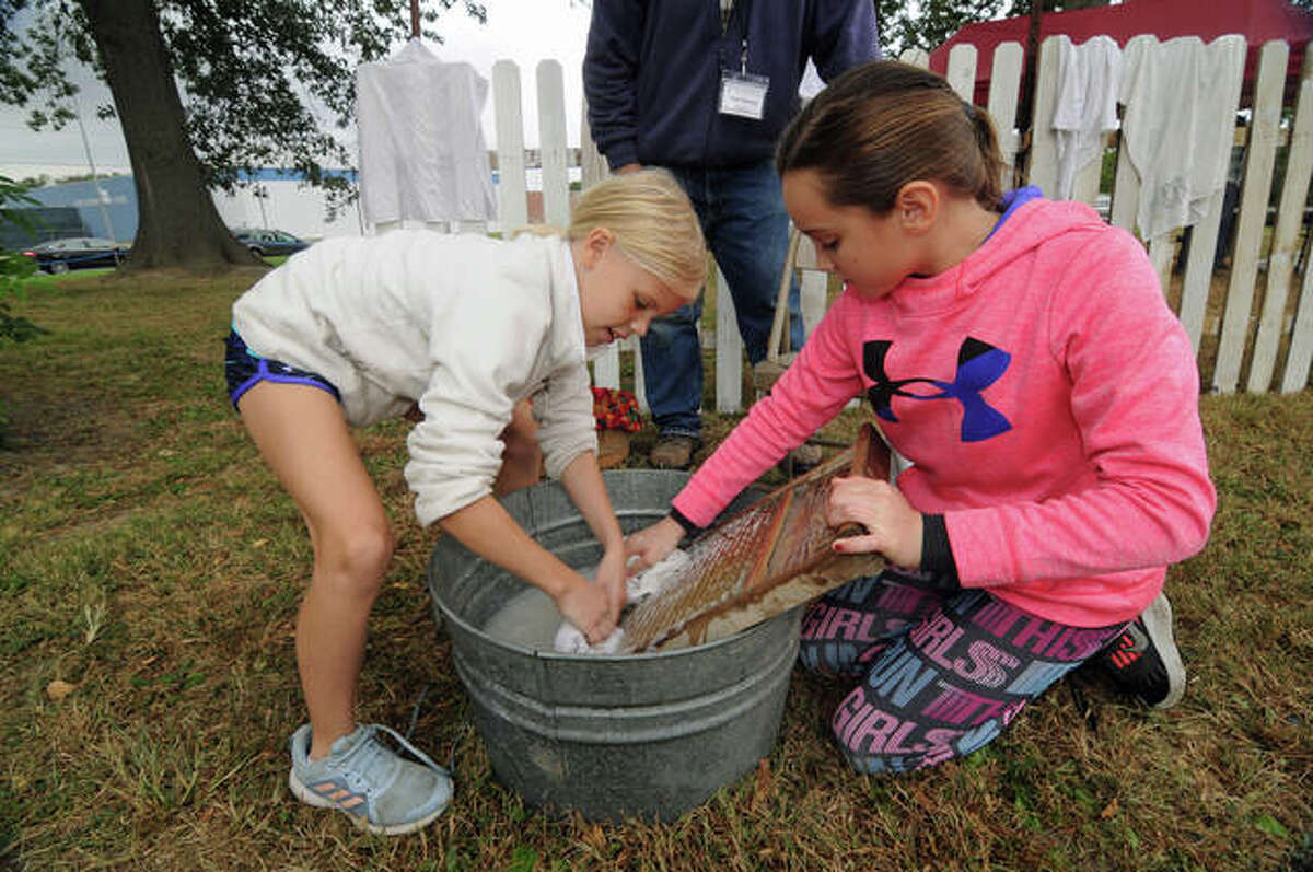 In this 2019 photo, Brenley Kelly, 9, left, and Marley Cazier, 10, both of Jerseyville, wash clothes the old-fashioned way on a washboard at the Jersey County Historical Society Apple Festival. This year's event is planned Oct. 2.