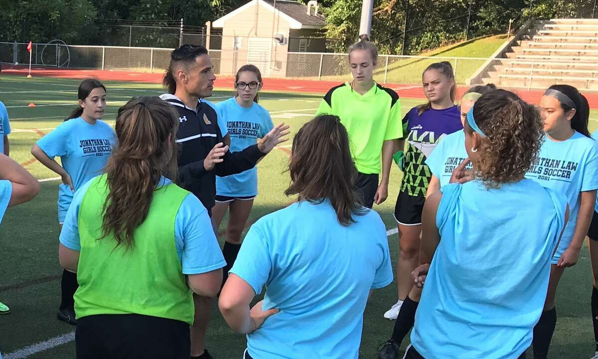 Law coach Joaquin Rodriguez goes over strategy with the Law girls' soccer team