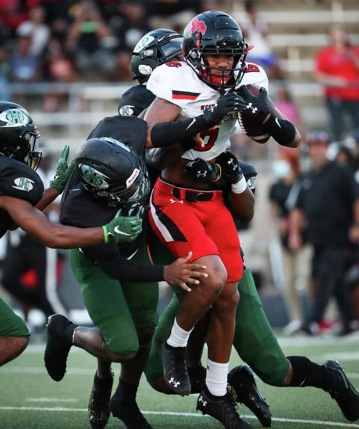 Westfield wide receiver Chuuky Hines (6) is stopped by Hightower defenders after hauling in a reception for a first down during the first half of a non-district high school football game at Hall Stadium Friday, Sept. 3, 2021 in Missouri City.