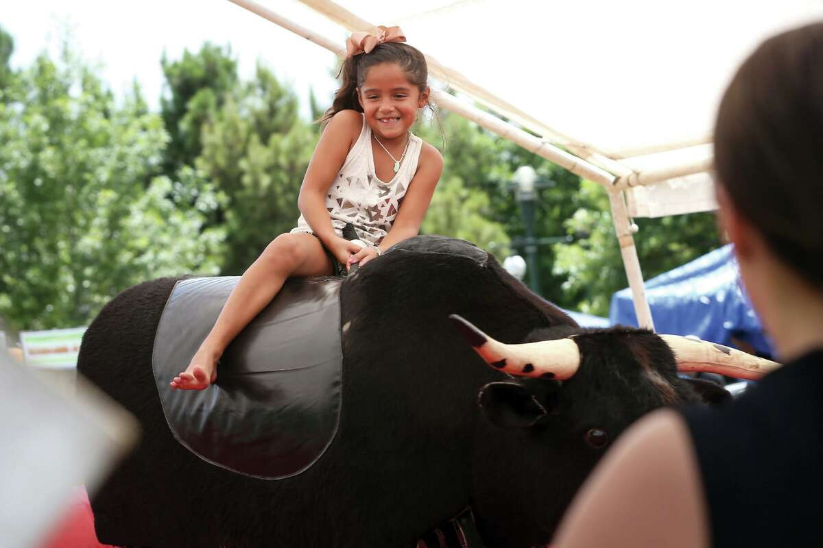 Cassandra Trevino, of The Woodlands, rides a mechanical bull during the Woodlands Family Fun Fest on Saturday, July 18, 2015, at Town Green Park.