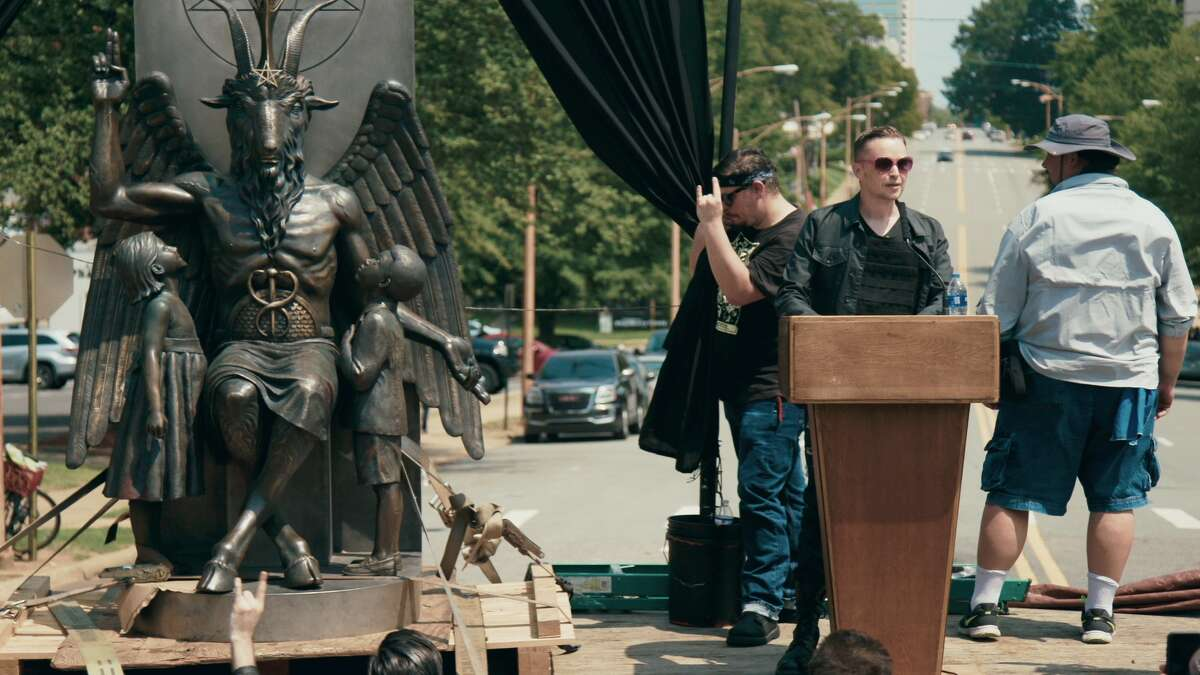 Satanic Temple co-founder Lucien Greaves (behind the podium) address the crowd at the unveiling of the Baphomet monument on the grounds of the state capitol in Little Rock, AR.