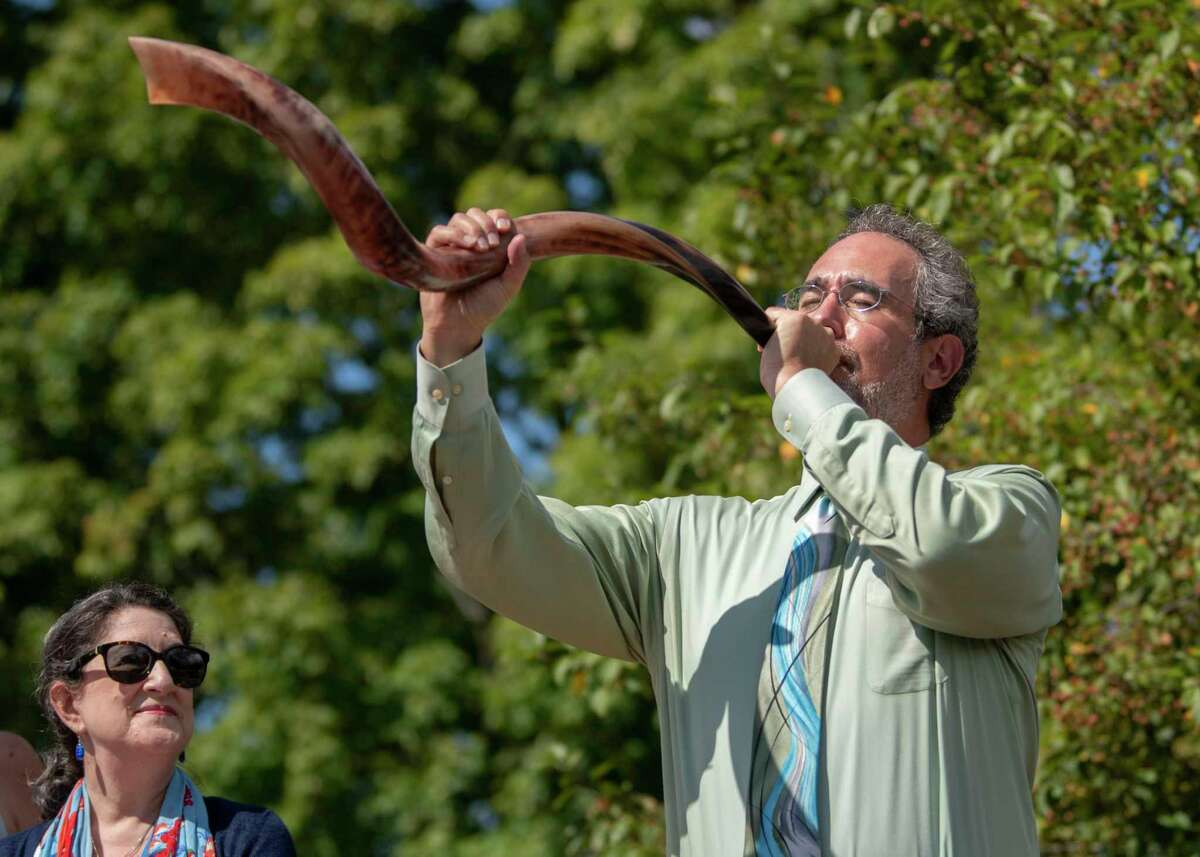 David Siegfeld blows his shofar to celebrate Rosh Hashana at temple Congregation Beth Emeth on Tuesday, Sept. 7, 2021 in Albany, N.Y. Cantor Sharon Kohn watches at left.