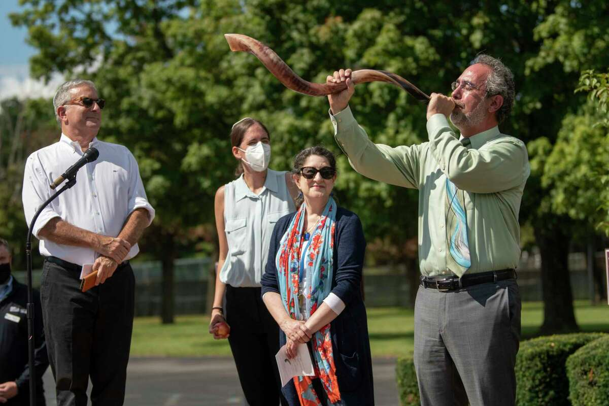 From left, Rabbi Scott Shpeen, rabbinic intern Alexandra Stein, and cantor Sharon Kohn listen as David Siegfeld blows his shofar to celebrate Rosh Hashana at temple Congregation Beth Emeth on Tuesday, Sept. 7, 2021 in Albany, N.Y.