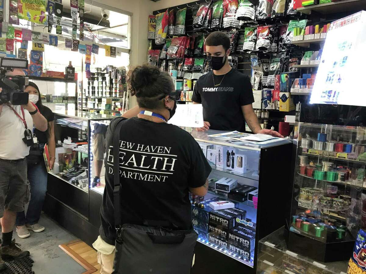 New Haven Senior Sanitarian Shellie Longo provides signs for Grab 'N Go Mart Smoke Stop clerk Zael Cortes to display around the store on Sept. 7, 2021, during a canvass of downtown businesses.
