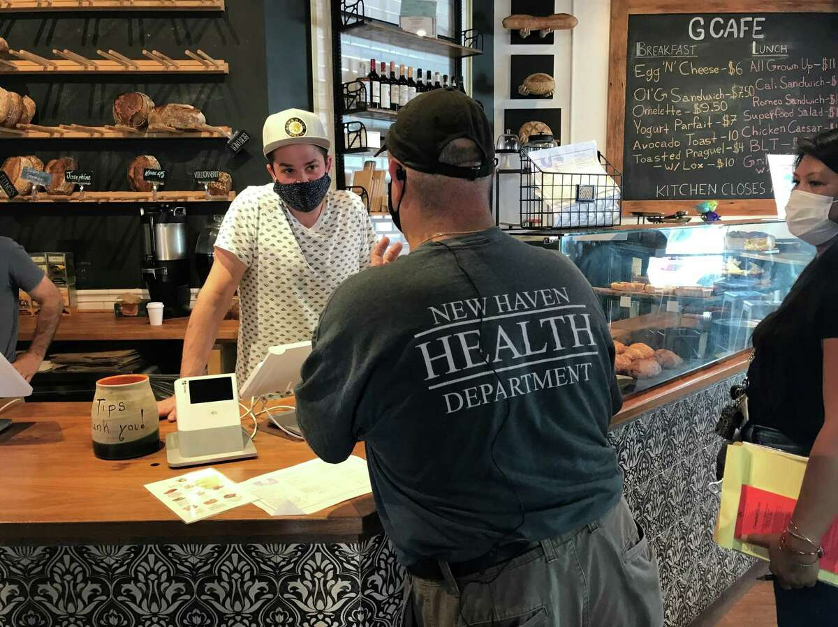 New Haven Senior Sanitarian Brian Mnek shares information about the city's mask mandate with G Cafe manager Tyler Demora on Sept. 7, 2021, during a canvass of downtown businesses.