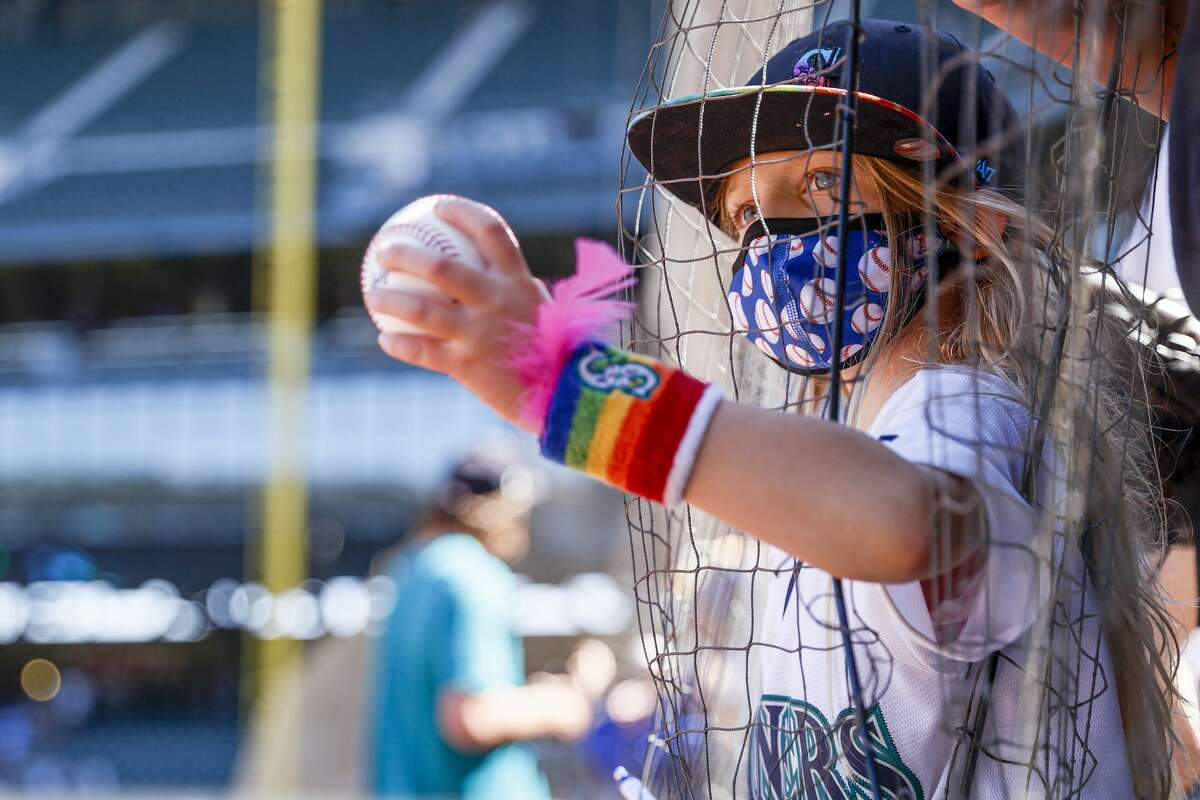 SEATTLE, WASHINGTON - AUGUST 28: A young fan reaches her baseball out to players for an autograph before the game against the Kansas City Royals at T-Mobile Park on August 28, 2021 in Seattle, Washington. (Photo by Steph Chambers/Getty Images)