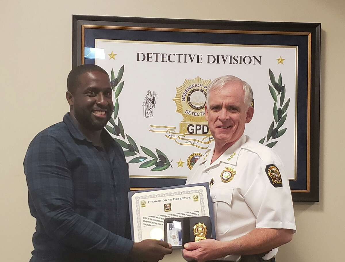 Det. Michael Hall, left, is presented with his detective's badge by Chief James Heavey.