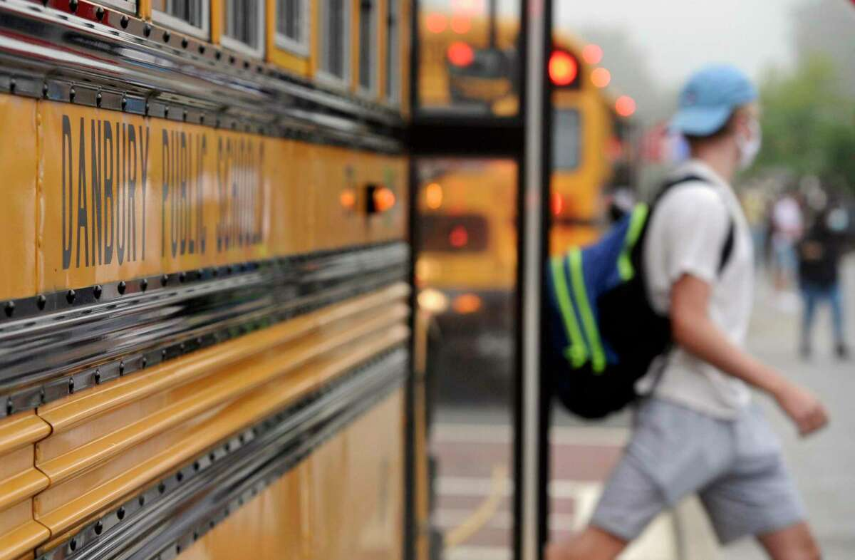 Students get off the buses at Danbury High School on the first day of the new school year. Monday, August 30, 2021, in Danbury Conn. Danbury reported 13 COVID cases in the first week of school.