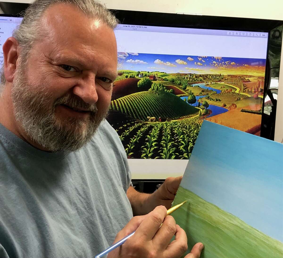 Local artist William Hattendorf offers a peek at the corner of the mural to be hung on the exterior wall of the Marilla Township Hall. The mural shown in the background is by Grant Wood and hints of what is to come. (Courtesy photo)